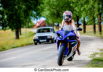 beautiful young woman with a motorcycle speed in nature