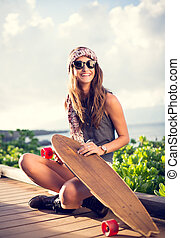 Beautiful young woman with a skateboard - Fashion lifestyle...