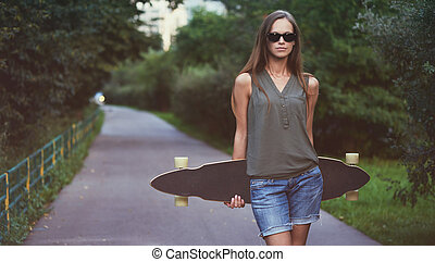 Beautiful young woman with a skateboard
