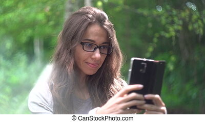Beautiful young woman with a smartphone in a summer park