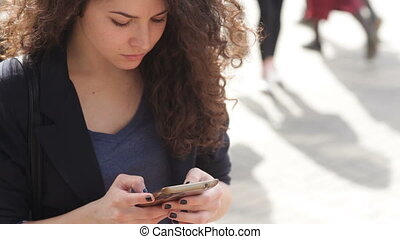 Beautiful young woman with a smartphone in the hands of the city