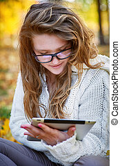 young woman with a tablet sitting in the autumn park - ...