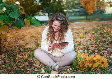 beautiful young woman with a tablet sitting in the autumn park
