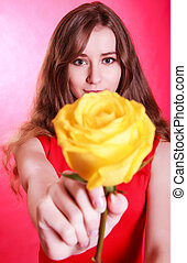 Beautiful young woman with a yellow rose