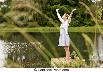young woman with arms outstretched by the lake - beautiful...