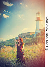 beautiful young woman with binoculars in front of wonderful lighthouse background