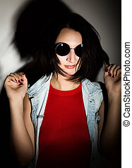 Beautiful young woman with black round sunglasses. Touching glasses.