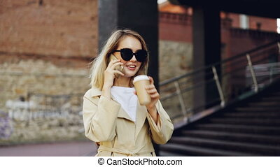Beautiful young woman with blond hair is talking on mobile phone and drinking take away coffee walking in city along street and enjoying drink and conversation.
