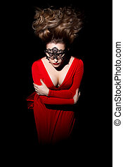 Beautiful young woman with blowing hair in a red dress -...