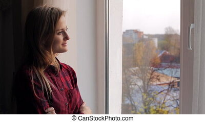 Beautiful young woman with book looking out the window and smiling