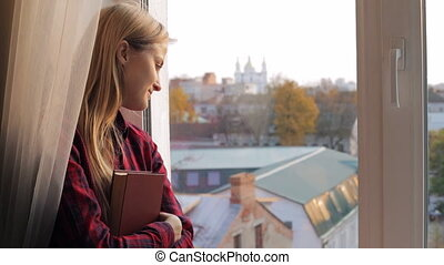 Beautiful young woman with book looking out the window
