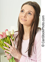 Beautiful young woman with bouquet of flowers