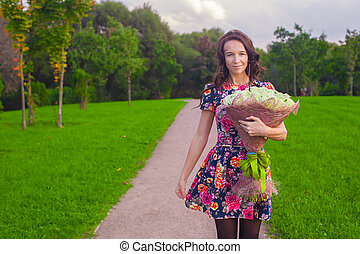 Beautiful young woman with bouquet of white roses