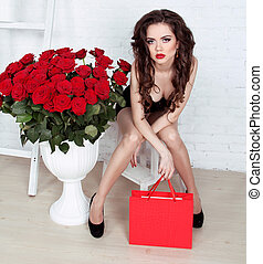 Beautiful young woman with bouquet of red roses and gift box, Valentine's day