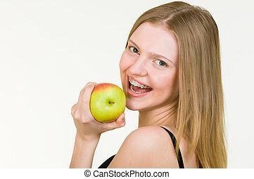 Beautiful Young woman with brackets eating apple