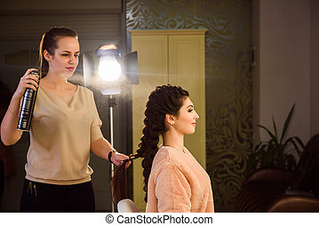 Beautiful Young Woman With Braid Hairstyle. Beautiful woman getting haircut by hairdresser in the beauty salon