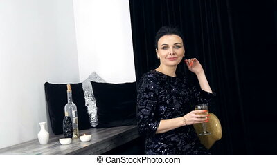 Beautiful young woman with bright evening make-up and a festive dress with a glass of white wine in her hands, who looks at the camera and poses