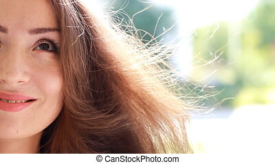Beautiful young woman with brown hair smiling on a windy...