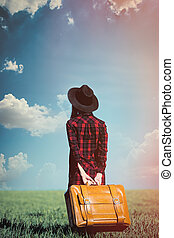 beautiful young woman with brown suitcase standing on the wonderful field background