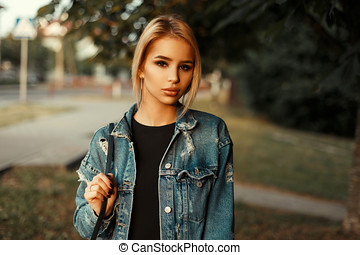 Beautiful young woman with clean skin in jeans clothes on a summer day