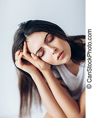 Beautiful young woman with closed eyes touching her face