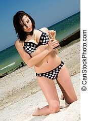 Beautiful young woman with coctail on a beach