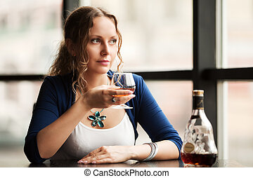 Beautiful young woman with cognac looking out the window
