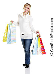 Beautiful, young, woman with colorful shopping bags in her hand , isolated on white