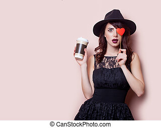beautiful young woman with cup of coffee and heart shaped toy on the wonderful pink background