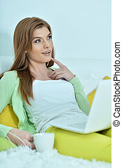 Beautiful young woman with cup of coffee and laptop
