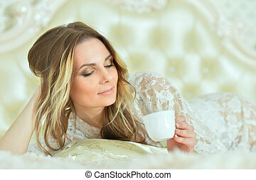 Beautiful young woman with cup of coffee in bed