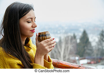 Beautiful young woman with cup of coffee on winter background