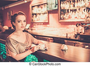 Beautiful young woman with cup of coffee near bar