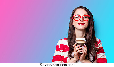 beautiful young woman with cup of coffee standing in front of wonderful blue background