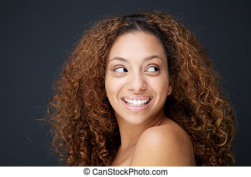 Beautiful young woman with curly hair laughing and looking away