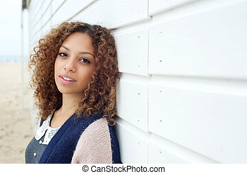 Beautiful young woman with curly hair posing outdoors