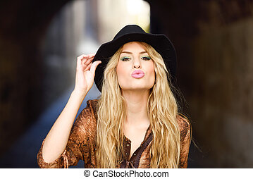 Beautiful young woman with curly hair wearing hat