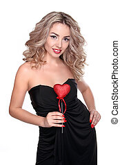 Beautiful young woman with curly long hair holding heart