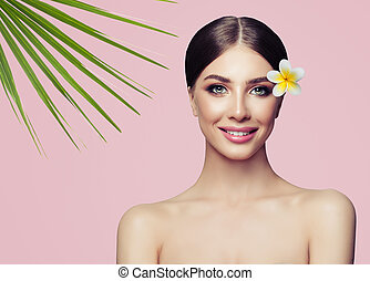 Beautiful young woman with cute smile, healthy skin and flower. Facial treatment and spa