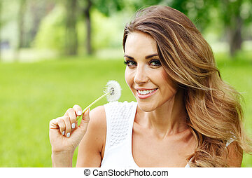 beautiful young woman with dandelion