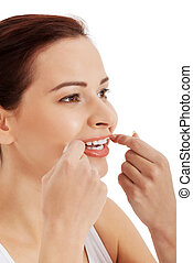 Beautiful young woman with dental floss.