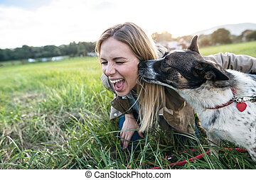 Beautiful young woman with dog in green sunny nature -...