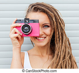 Beautiful young woman with dreadlocks taking photos with vintage pink retro film camera