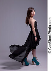 beautiful young woman with dress on wind, looking to camera, studio shot