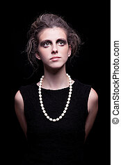 beautiful young woman with elegant black dress, on black background, studio shot