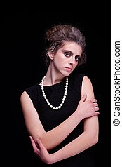 beautiful young woman with elegant black dress,to hold up.  on black background, studio shot