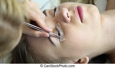Beautiful young woman with eyelash extension. Woman eye with long eyelashes. Beautician eyelash extension for young woman in a beauty salon