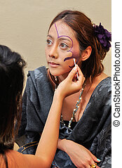 Beautiful young woman with fashion make-up by a beautician