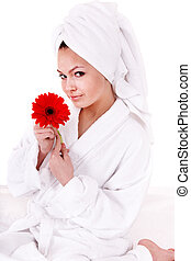 Beautiful young woman with flower in spa.
