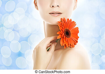 Beautiful young woman with flower over abstract blue background